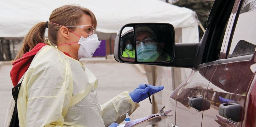 nurse talking to someone in vehicle